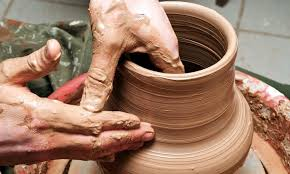 person turning clay on a potters wheel