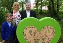 photo of Emily and her parents with her winning design in Jubilee Park