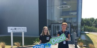 two ladies holding a poster of The Deal outside The Edge in Wigan