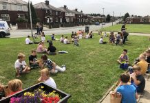 photo of Children having their provided lunch outside Dorset Road Community Centre.