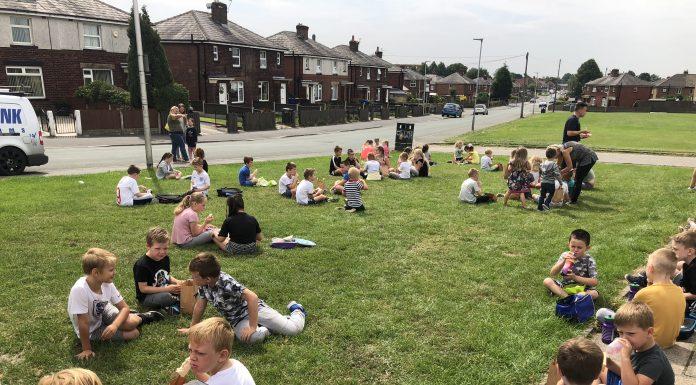 photo of Children having their provided lunch outside Dorset Road Community Centre.