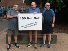 photo of Gordo holding a poster saying 100 not out