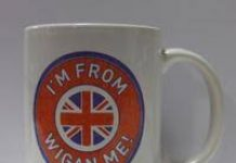 white mug with red circle in which is written I'm from Wigan Me