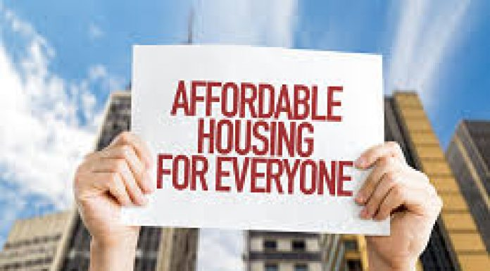 person holding up a poster saying affordable housing