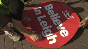 red and white words saying believe in Leigh