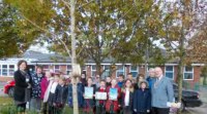 Photo: left to right: Teachers, children with Wigan Rotary President Mervyn Reeves in the grounds of Millbrook Primary School