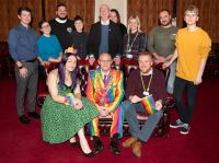 The Mayor of Wigan borough in his rainbow suit with Alex Miller from Wigan and Leigh archives and members of Wigan Pride Committee
