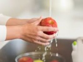 photo of someone washing an apple